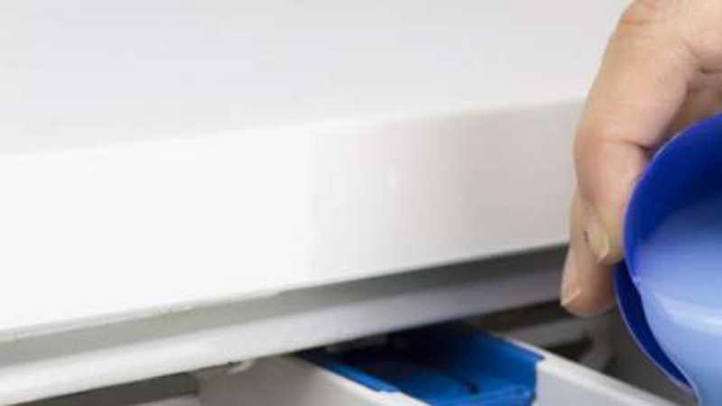 Person som häller flytande tvättmedel i tvättmaskinlådan
