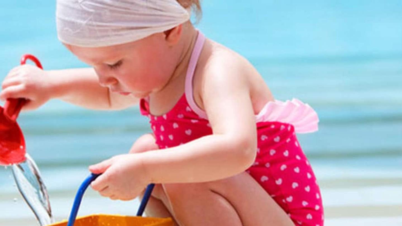 En flicka sitter i en pool och leker med hink och spade