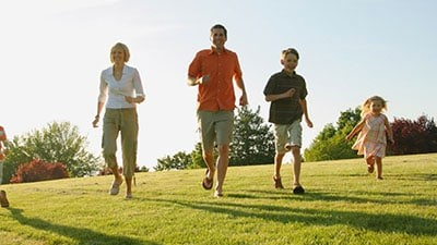 Föräldrar och barn som springer över ett fält