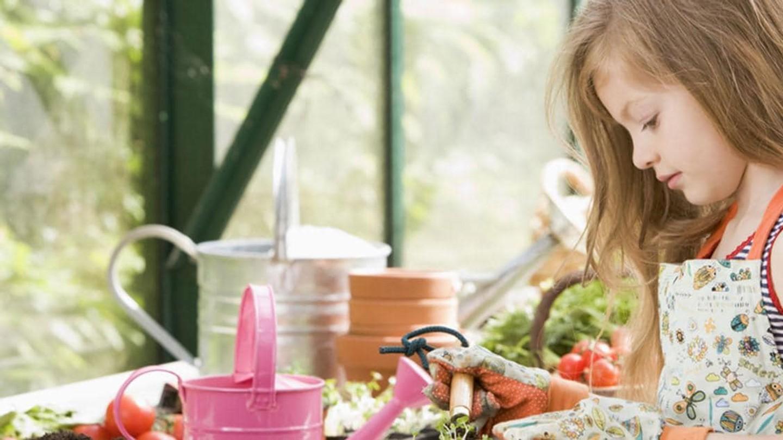 En flicka som planterar i ett växthus