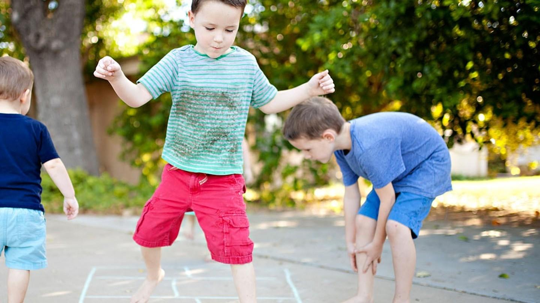 En pojke i lerig t-shirt som spelar barfota med sina vänner