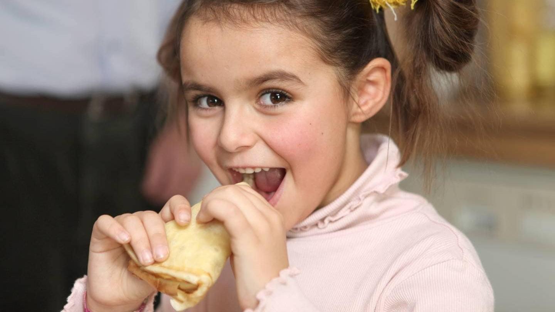 En flicka äter ett bakverk