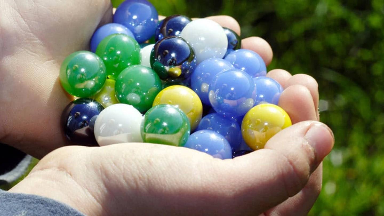 Ett par kupade händer med färgglada kulor