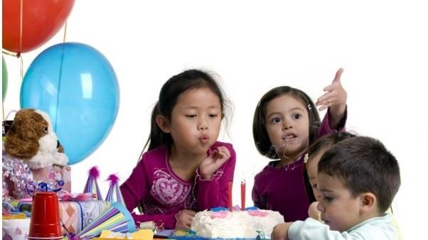 En tjej som blåser ut ljus på sin födelsedagstårta