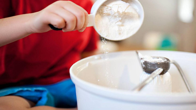 Ett barn häller en skopa mjöl i en matberedare