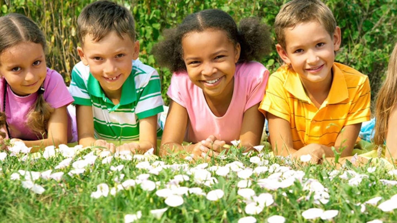 Fem barn ligger på ett fält täckt av vita blommor